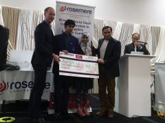 Rosemere Cancer Foundation's chief officer Dan Hill accepts a donation from Zehran and Ayesha Punekar watched by their father Mr Maqsood Punekar