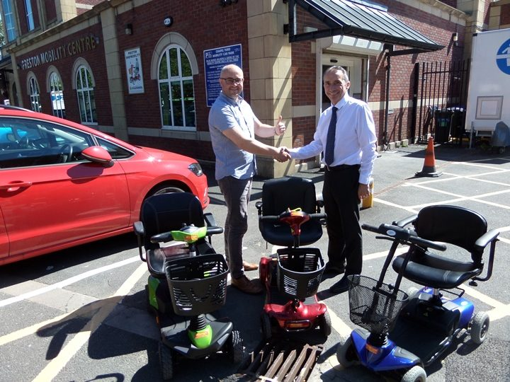 Joe Hannett (left) from Preston Shopmobility receives the donation from Jim Rolfe of Millercare