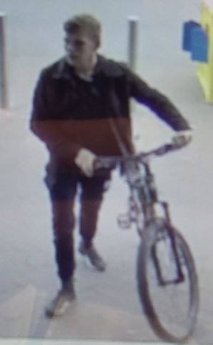 The man police want to speak to is seen wheeling a bike from the store