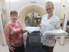 Treatment Delivery Team Leader Kelly Littlefair (right) hands over the Radiotherapy Department's stock of new Rosemere Cancer Foundation funded gowns to Treatment Planning Team Leader Catherine Abbott