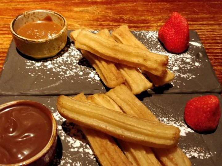Two portions of churros with dulce de Leche and chocolate sauce