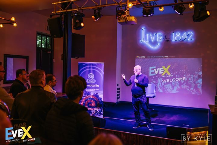 A speaker on stage at the September EveX Network