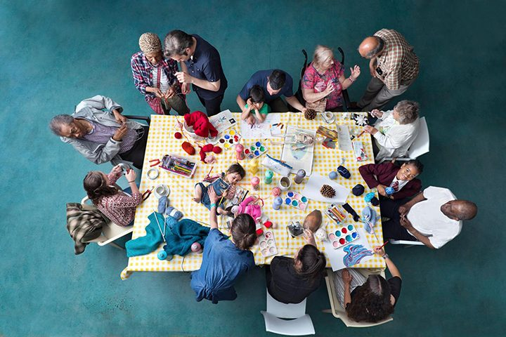 Photo from above of a table with activity and people of all ages