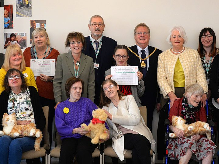 Group shot including robo-pets at a Lancashire County Council reception to celebrate International Day for Older People