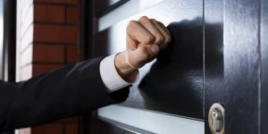 Door-to-door salesperson knocking on door