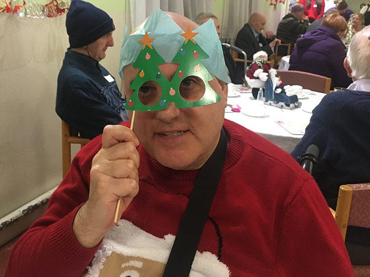 A partygoer having fun with Christmas props