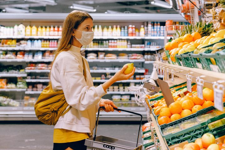 A woman shopping for food in a face mask