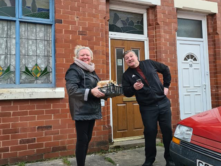 Elizabeth and Brian outside a house delivering a food basket to one of their regular customers