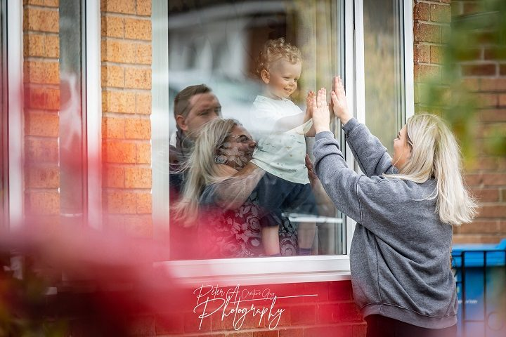 Charlotte reaches up to greet her son who is behind the window of her parent's house Pic: Peter Austin