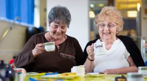 Two pensioners being made a cup of tea before social distancing was introduced Pic: People's Health Trust