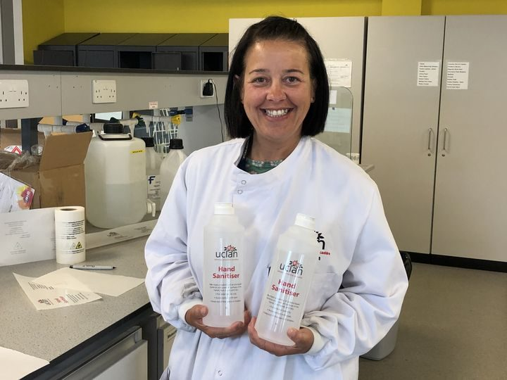 Technician Terri Blohm with the labelled bottles of hand sanitiser