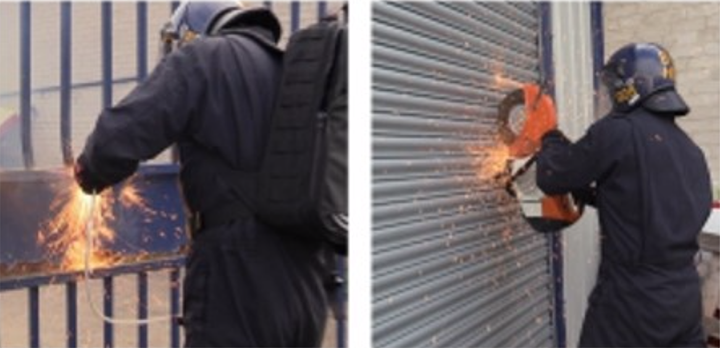 An officer cuts through a roller shutter to get into the unit