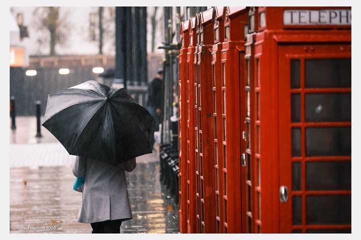 Walking with an umbrella past Preston's red phone boxes on Market Street Pic: Paul Melling