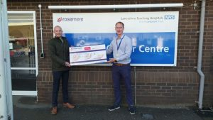 Festive cheer from John (right) presenting his donation to Rosemere Cancer Foundation's chief officer Dan Hill outside Rosemere Cancer Centre, where his much loved and missed mum Janet was treated earlier this year