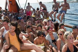 An afternoon boat party for the many British seasonal bar workers and promoters in Ayia Napa, Cyprus. They are performing a dance to the 1979 funk anthem recorded by The Gap Band, Oops Up Side Your Head