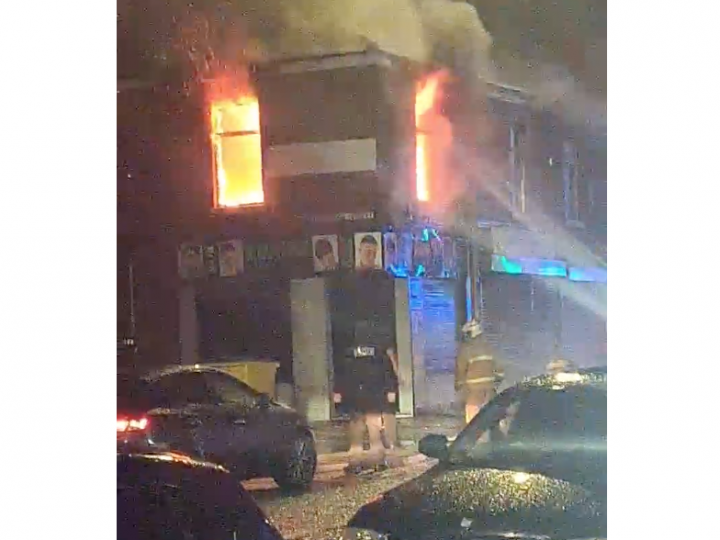 Flames escape from the windows of the flat above Adams Hair Salon
