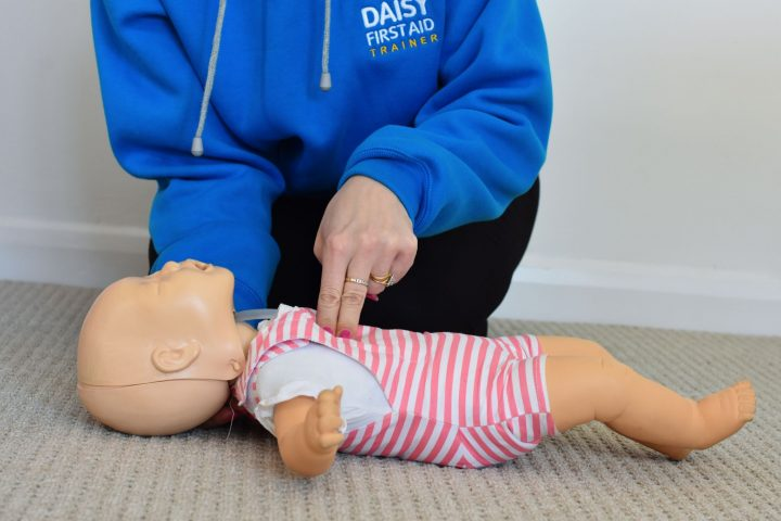 Practising baby first aid on a doll